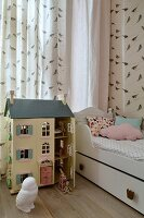 Girl's bedroom in pastel shades with princess bed, bird-patterned wallpaper and dolls' house