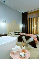 View past free-standing bathtub and side table to double bed with curved headboard