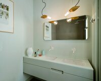 Twin washstand with undermount sinks below square mirror with rounded corners