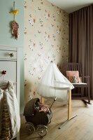 Butterfly wallpaper, cradle, rocking chair and dolls' pram in nursery
