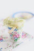 Home-made elderflower ice lilly lying across floral beaker