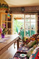Colourful patterned textiles in comfortable, ethnic-style living room with view through open terrace doors