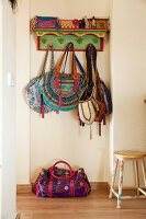 Various ethnic handbags hanging on brightly painted wooden coat rack