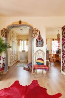 View into two rooms, pink cowhide rug, ethnic blanket on chair and painted archway