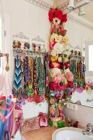 Collection of colourful hippie necklaces and garland of fabric flowers in bathroom