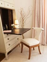 Elegant, feminine writing area with elegant bureau and upholstered chair