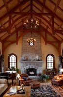 Grand, high-ceilinged, country-house interior with historical ambiance, stone fireplace and exposed rood structure