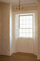 Bay window with elegant, panelled cladding and fitted cupboard