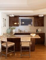 Country-house kitchen with glossy, brown fronts, breakfast bar and wall-mounted, flatscreen TV