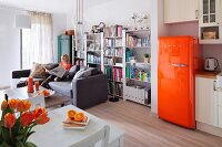 Open-plan living area with orange retro fridge; woman sitting on couch in front of bookcase