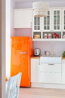 Orange retro fridge providing splash of colour in white, country-house kitchen