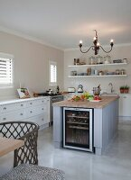 Free-standing island counter with integrated wine refrigerator below chandelier in white, country-house kitchen
