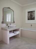 Masonry washstand with countertop basin below mirror with antique, carved frames in bright bathroom