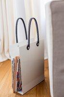 Stylised shopping bag magazine rack on parquet flooring