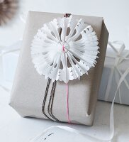 Hand-made, pleated paper stars with cut-out patterns as festive decoration on wrapped gift