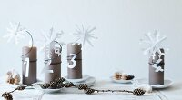 Paper snowflakes and letters on Advent pillar candles
