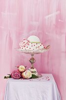 Romantic, festive cake on elegant cake stand decorated with roses