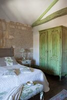 Stone walls, green-painted roof beams and antique wardrobe painted a matching green in Mediterranean bedroom