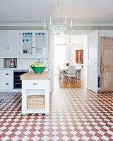 Island counter and red and white chequered floor in spacious kitchen with view into dining room through open door