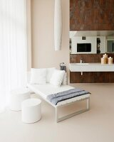 White chaise and side table in luxurious bathroom with rust-effect tiles