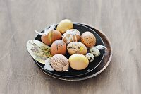 Easter eggs painted using natural dyes & decorated with ribbons & feathers