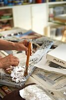 Hands of person applying silver leaf to picture frame in artist's studio