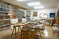 Artist's studio with tins of paint and plastic storage boxes on shelving and various wooden picture frames