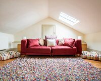 Many scatter cushions on red couch and multicoloured rug in attic room with skylight