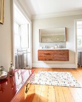 Floating wooden washstand, patterned rug on wooden floor and trunk painted a glossy red in foreground