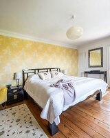 Double bed against wallpaper with floral pattern on yellow background in rustic bedroom