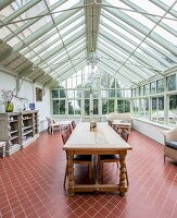 Long wooden table with turned legs in large conservatory with terracotta floor