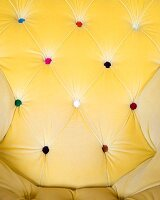 Backrest of button-tufted armchair upholstered in yellow fabric with buttons of various colours
