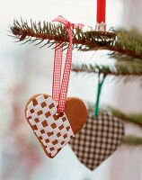 Gingerbread heart decorated with chequered icing hung on Christmas tree