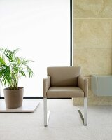 Modern cantilever chair with beige leather cover and metal legs in front of large window in stone wall
