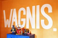 Vintage toys on top of blue cabinet below motto on orange wall