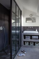 Grey bathroom with separate shower area and open-fronted concrete shelves with integrated sink