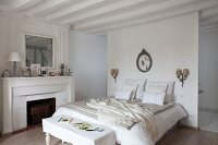 White, rustic bedroom with open fireplace and ensuite bathroom behind partition