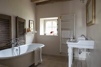 Free-standing vintage bathtub and sink on china legs in rustic bathroom