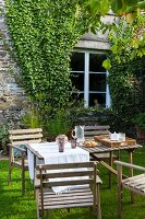 Wooden table and chairs in garden outside stone house with ivy-covered façade