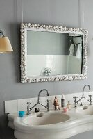 Vintage-style twin sinks with vintage-style tap fittings below mirror with frame decorated with seashells