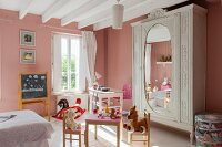 Pink walls, play table and antique wardrobe in vintage-style child's bedroom