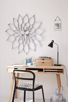 A homemade wall clock inspired by classic design with a corrugated, silver paper creating a flower frame hanging above a small desk