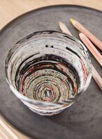 A birds-eye view of a homemade pencil pot made from folded strips of newspaper stuck together