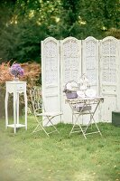 Garden table, ornate metal chair, vintage screen and vase of hydrangeas on side table