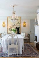 White tablecloth on dining table, white-painted chairs and antique chandelier in traditional dining room