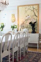 White-painted chairs with arched backrests around dining table in traditional dining room with painting on wall in background