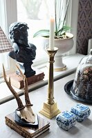 Roebuck hunting trophy, white and blue china pots, brass candlestick and bust on windowsill