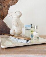 China rabbit, hairbrush and perfume bottles on stone dish