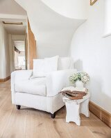 White armchair and rustic wooden stool below staircase in hallway of country house