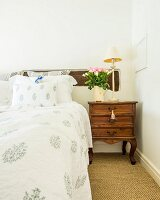 Vase of roses and lamp on antique bedside table